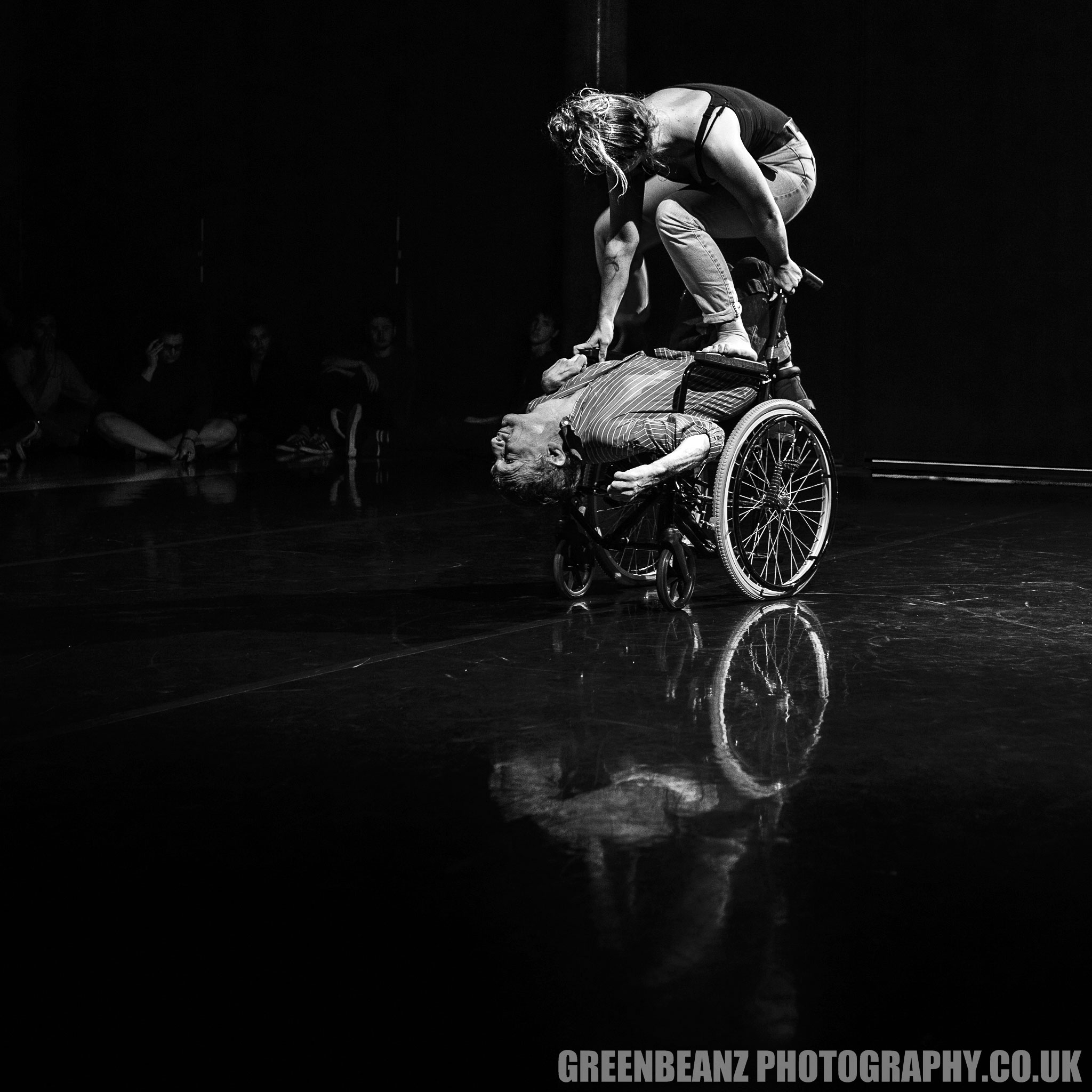 Cloey stnad on Kevin's Wheelchair during dance sequence