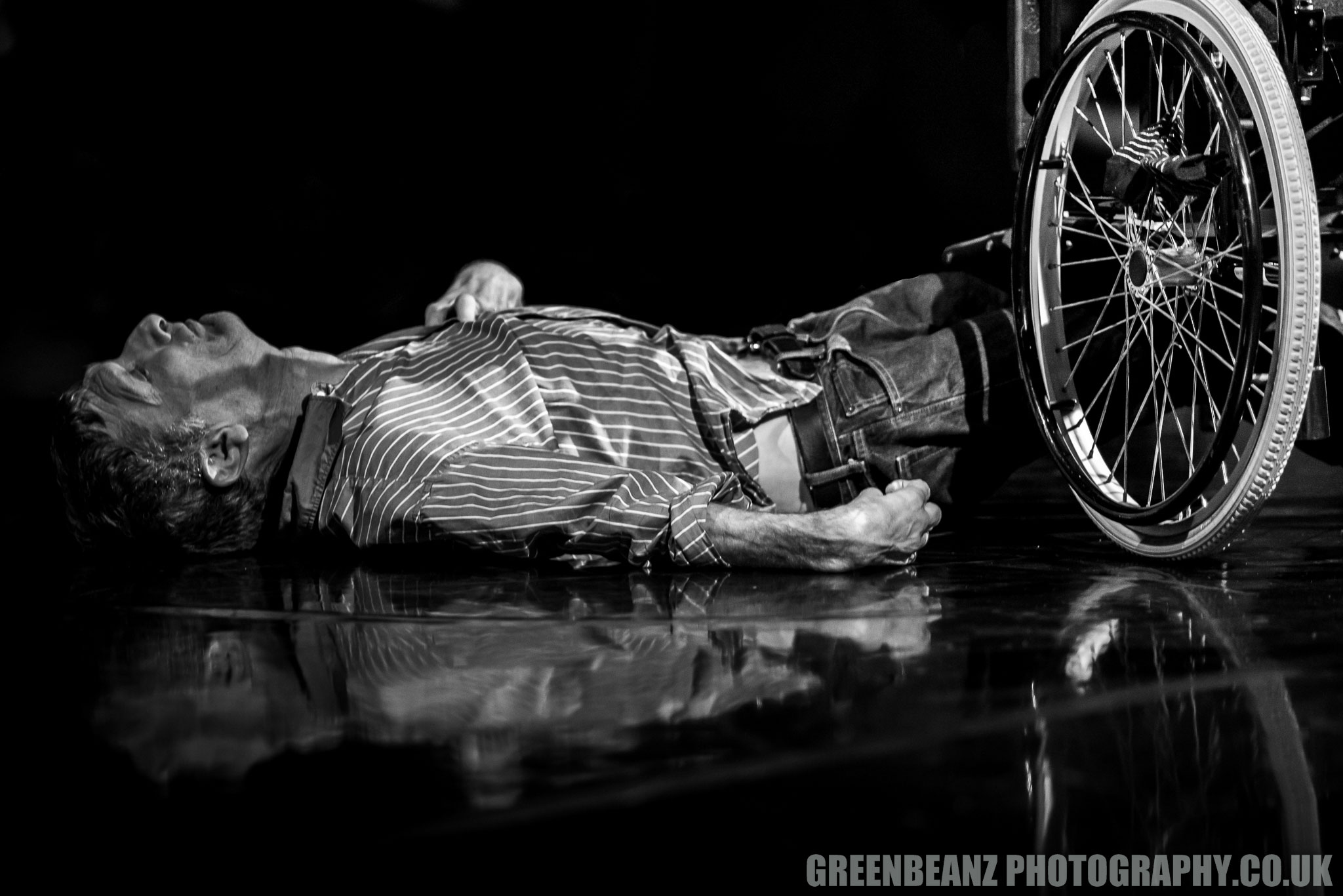 Black and White Photograph ofdisabled dancer on floor next to wheelchair