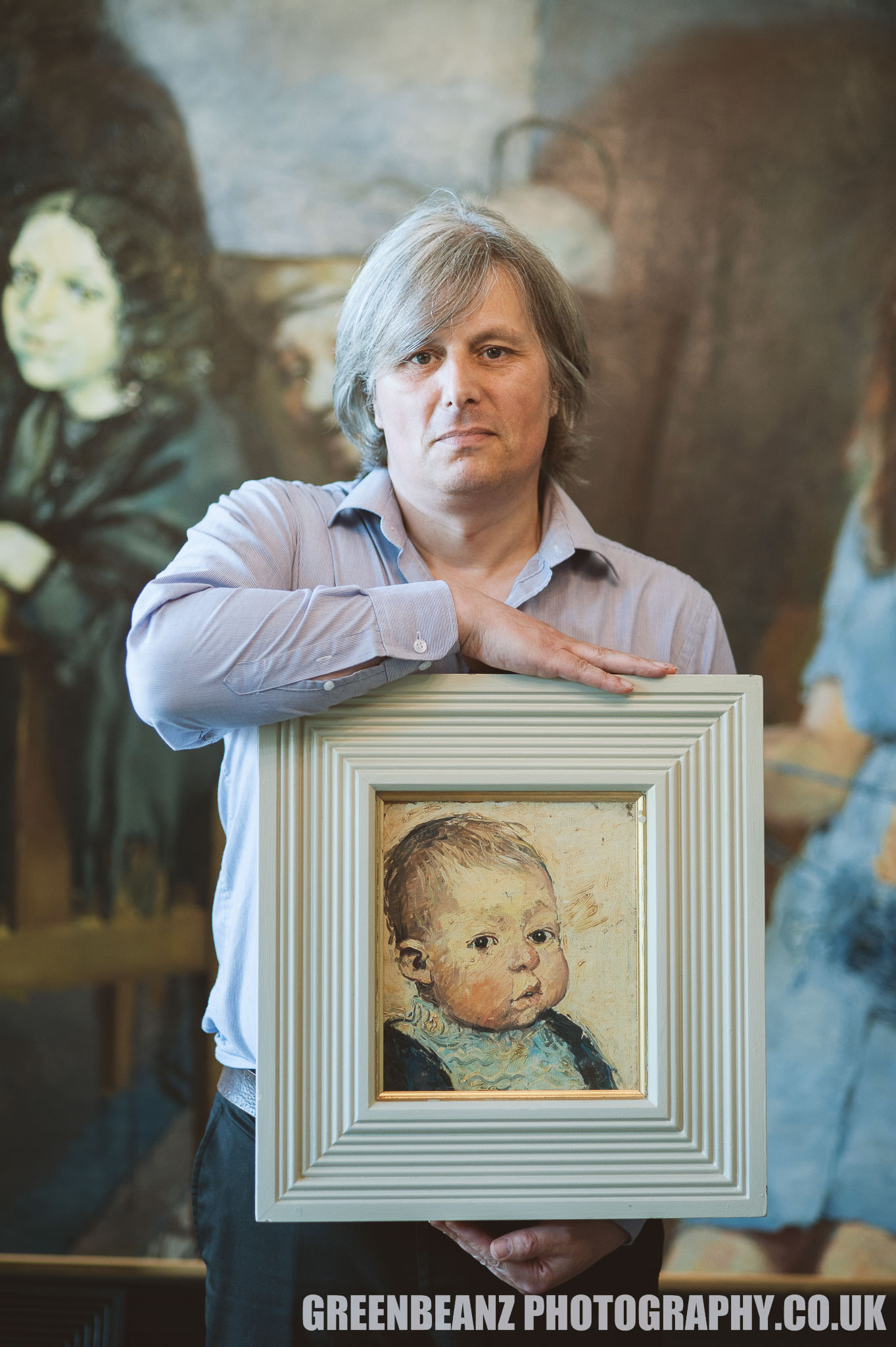Reuben Lenkiewicz holds a portrait of himself as a baby painted by father Robert